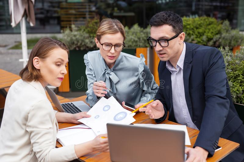 Three corporate leaders watching new business schemes. Corporate leaders. Three prosperous corporate leaders feeling inspiration while watching new business royalty free stock photography