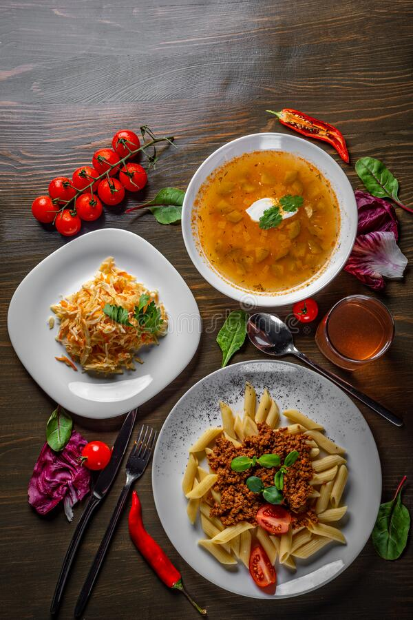 Three-course set on a table. Tasty lunch set made of three meals, such as soup,  salad and pasta penne stock photography