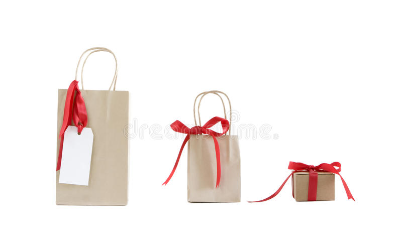 Three craft paper bags with red ribbons