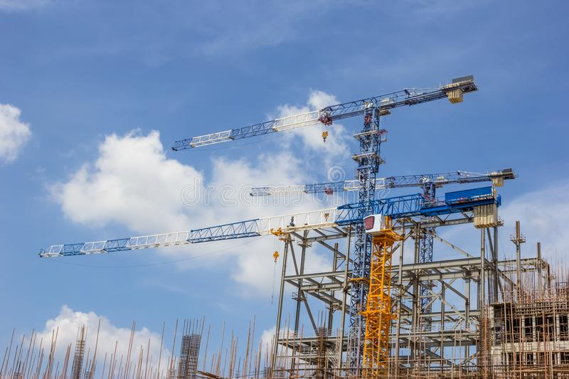 Three cranes on construction site with blue sky cloud royalty free stock image