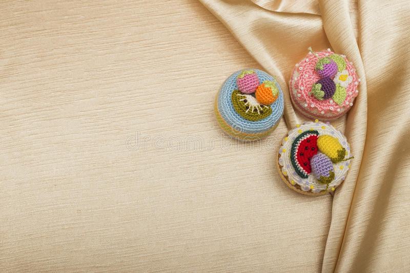 Three crocheted cakes on the silk royalty free stock images