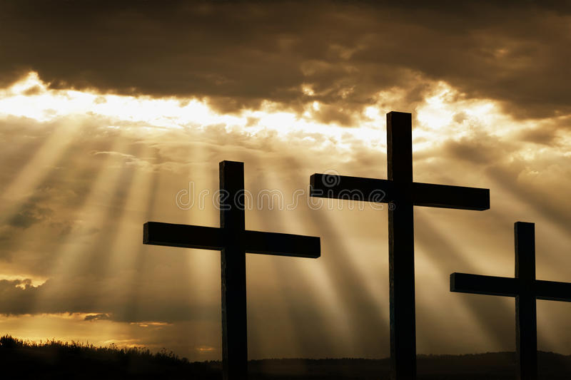Three Crosses Silhouetted Against Breaking Storm C. Dramatic sky silhouettes three wooden crosses with shafts of sunlight breaking through the clouds. A dramatic royalty free stock image