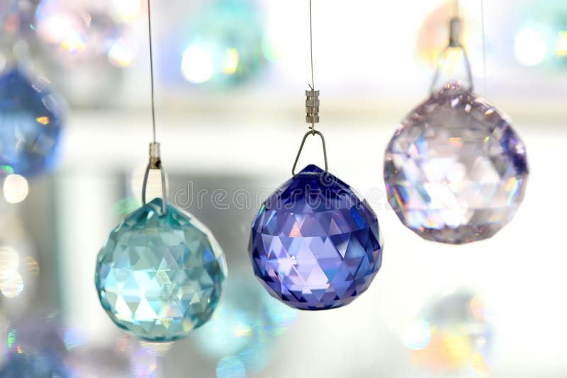 Three crystal ornaments hung on string. Selective focus close up of green, blue and clear crystal ornaments hung on string in store display stock photos