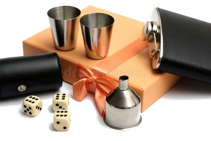 Three cubes and small leather bottle with two metal tow at orange giftbox. On white background stock images