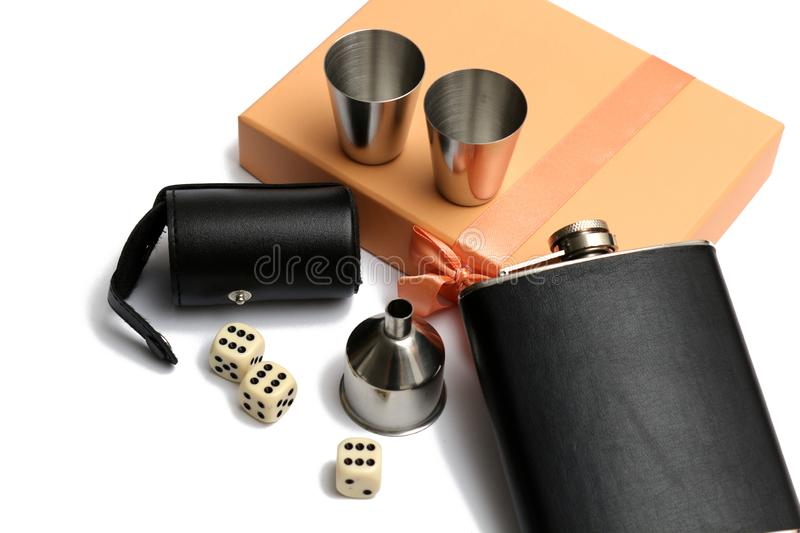 Three cubes and a  small leather hip flask with metal mugs at orange giftbox. On a white background royalty free stock photography