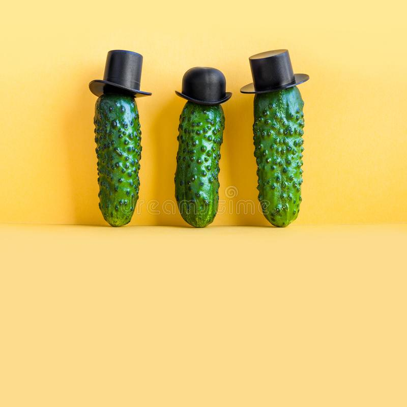 Three cucumbers old fashioned characters with black hats. yellow background, creative design food poster. copy space. Three cucumbers old fashioned characters stock photo