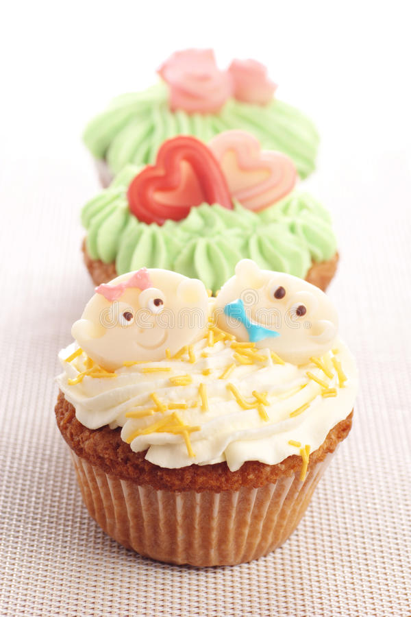 Three cupcakes decorated with icing and marzipan decorations. royalty free stock images