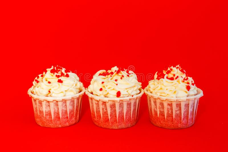 Three cupcakes with delicate white cream on a red background.  royalty free stock image