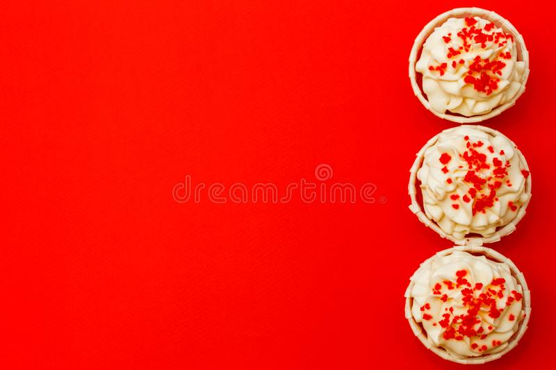Three cupcakes with delicate white cream on a red background.  stock photos