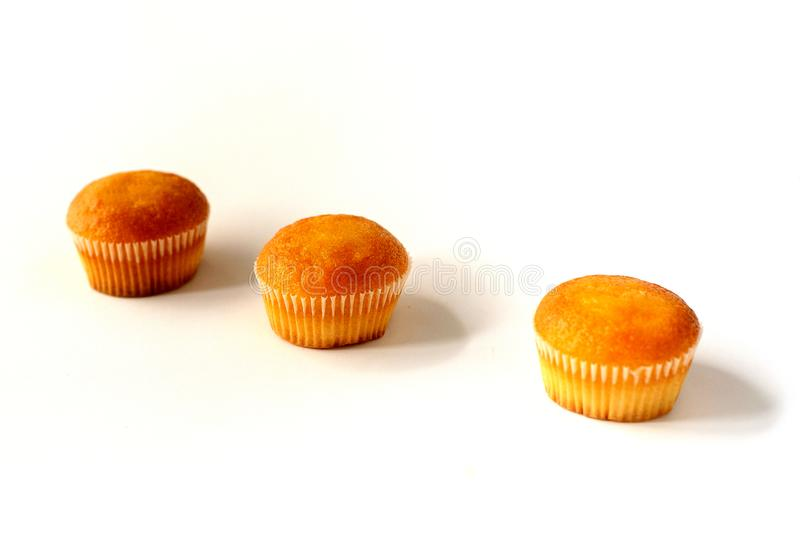 Three cupcakes with different fillings, side view in perspective, on a white background stock photo