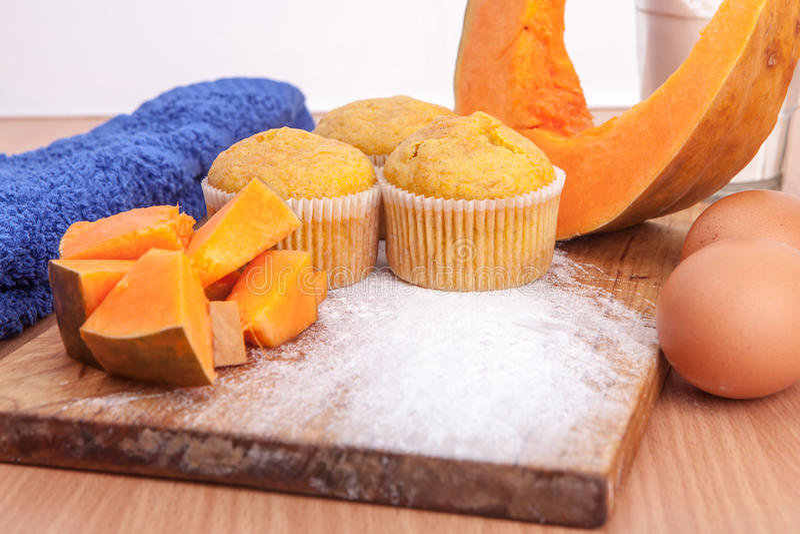 Three cupcakes, pumpkin and baking kitchenware on kitchen stock image