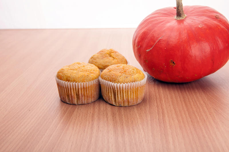 Three cupcakes and pumpkin on wood texture table royalty free stock image