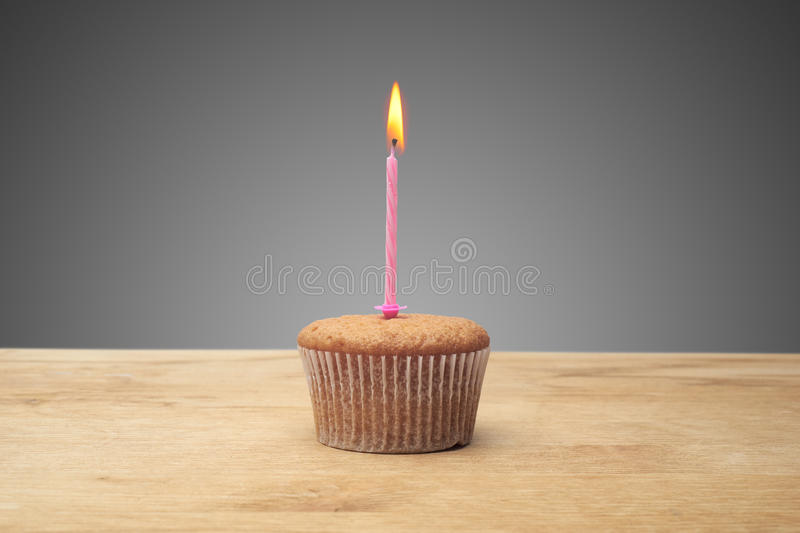 Three cupcakes on a wooden table royalty free stock photography