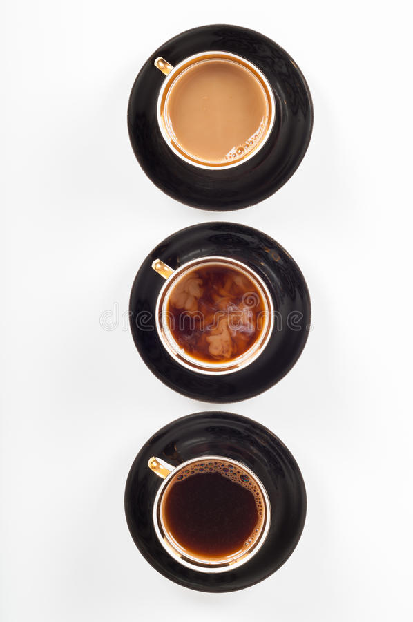 Three cups of coffee with black, white and flowing milk stock photo