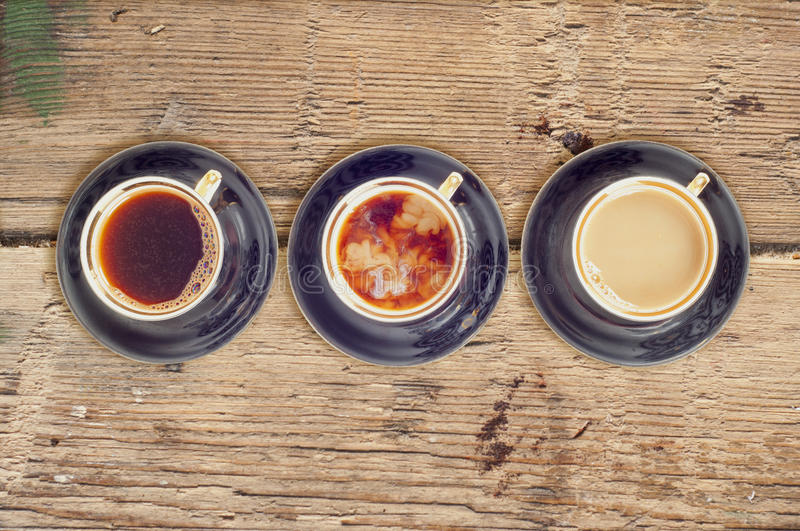 Three cups of coffee with black, white and flowing milk royalty free stock photography