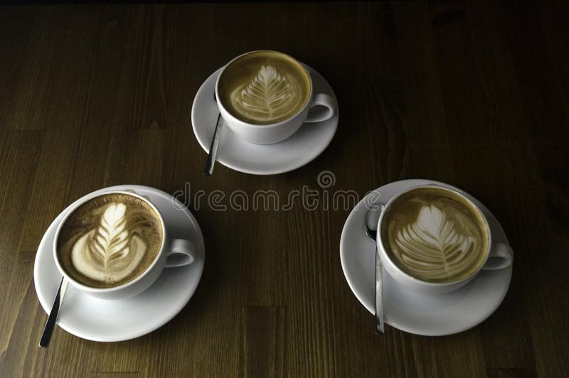 three cups ready to be served coffee with milk royalty free stock image