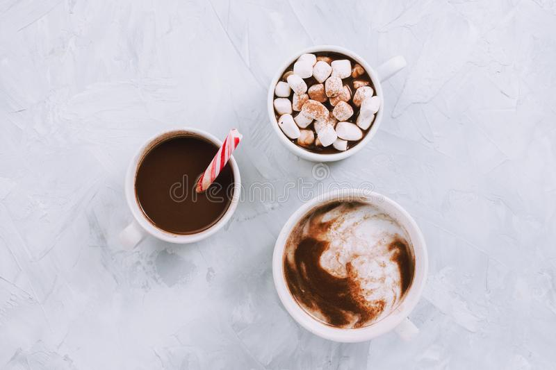 Three cups of vegan hot chocolate or cocoa with different toppings. On grey stock photography