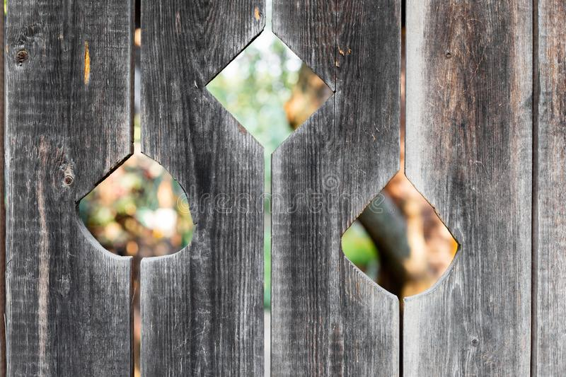 Three cut flower-shaped holes on wooden door of the old barn. Three cut flower-shaped holes on the wooden door of the old barn royalty free stock images