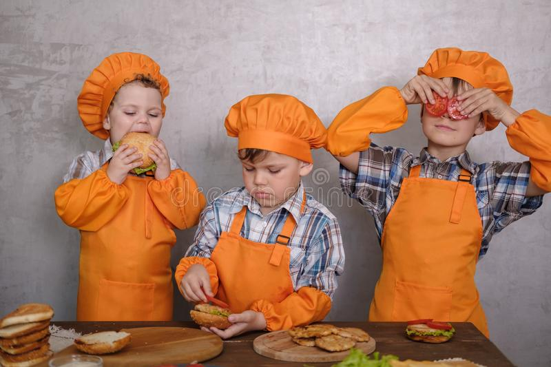 Three cute boys in costumes cooks engaged in cooking homemade burgers royalty free stock photos