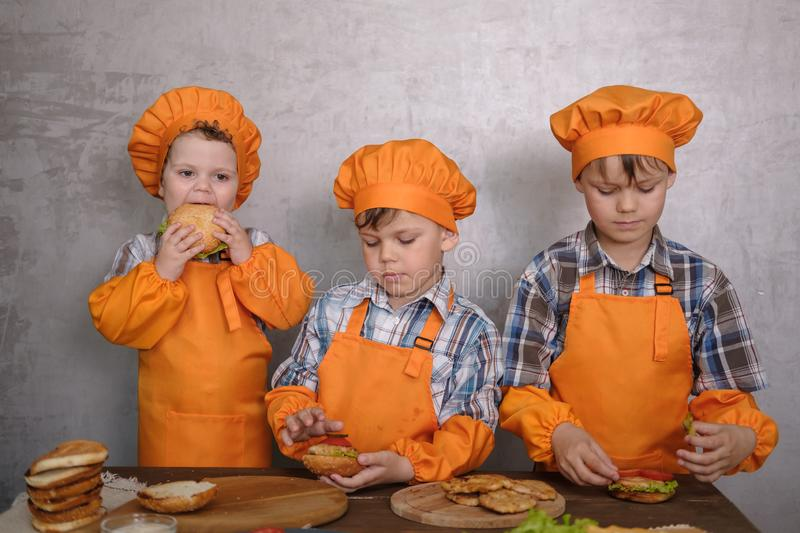 Three cute boys in costumes cooks engaged in cooking homemade burgers royalty free stock photography