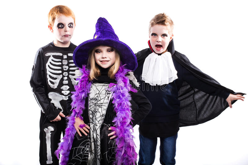 Three cute child dressed the Halloween costumes: witch, skeleton, vampire royalty free stock photography
