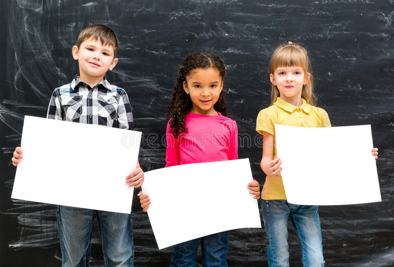 Three cute children with empty paper sheets in hands stock images