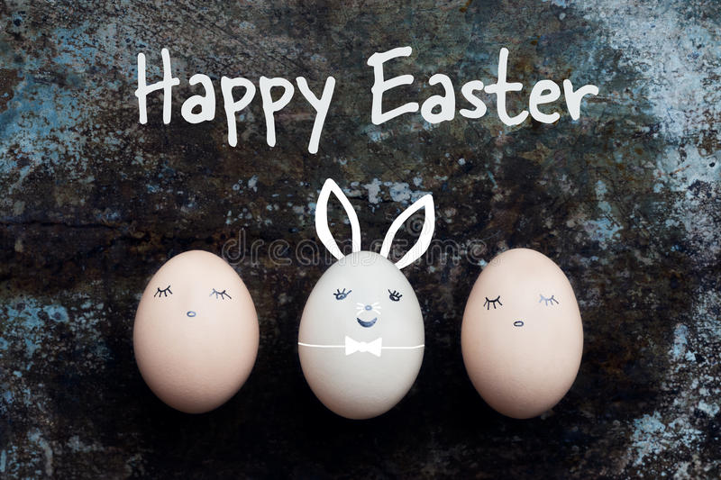 Three cute easter eggs with faces, happy easter bunny background royalty free stock image