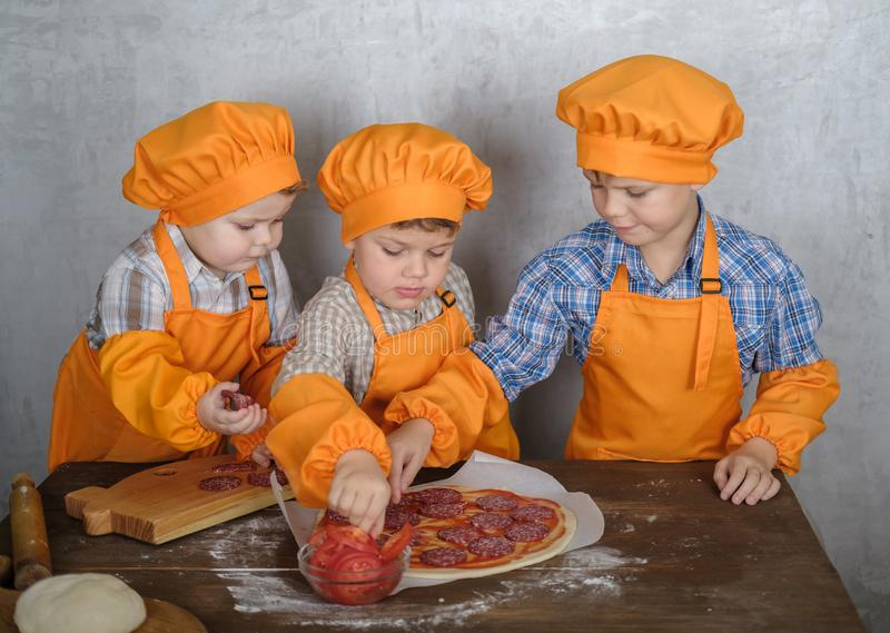 Three cute European boys dressed as cooks are busy cooking pizza. three brothers help my mother to cook pizza stock photos