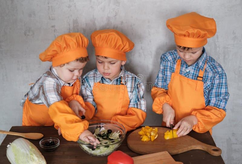 Three cute European boys in orange costumes cook prepare vegetable salad stock image