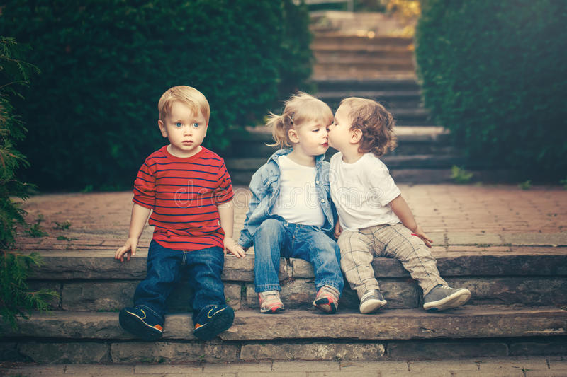 Three cute funny adorable white Caucasian children toddlers boys girl sitting together kissing each other royalty free stock photos