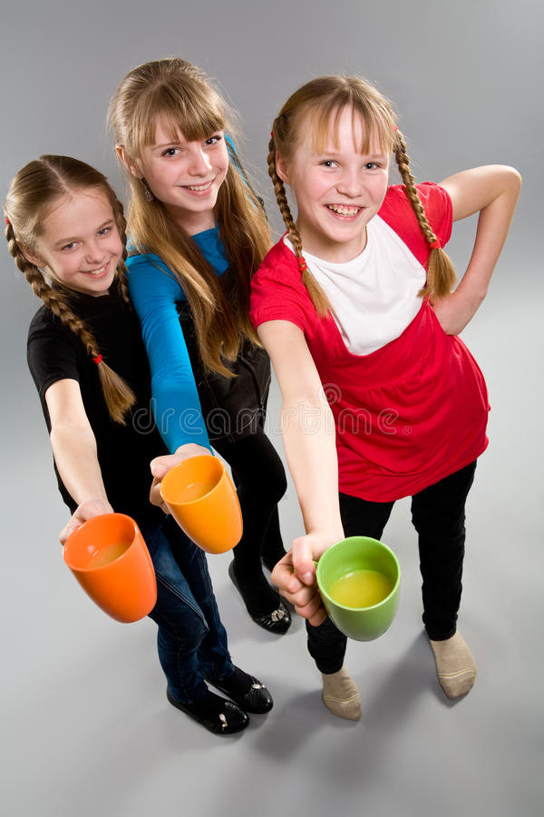 Three cute little girls with mugs royalty free stock image