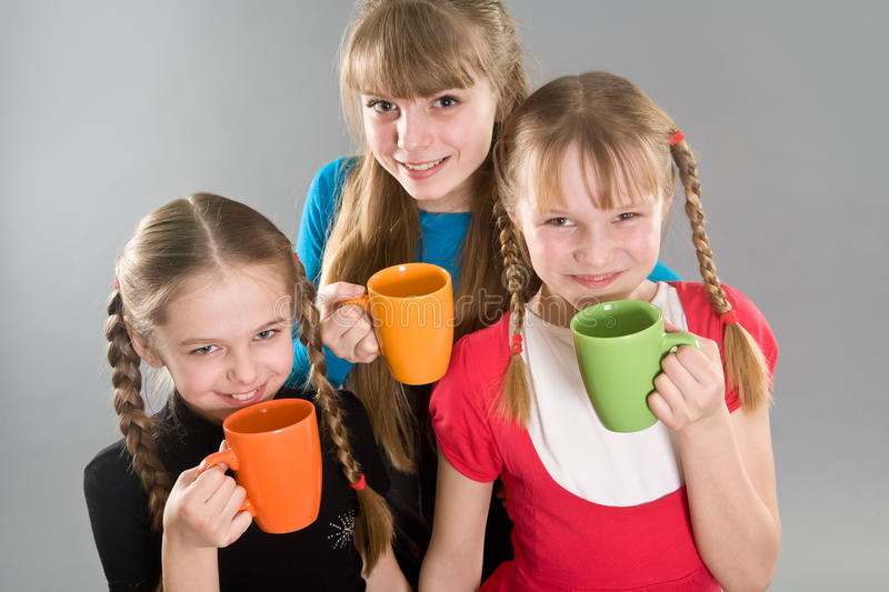 Three cute little girls with mugs royalty free stock photography