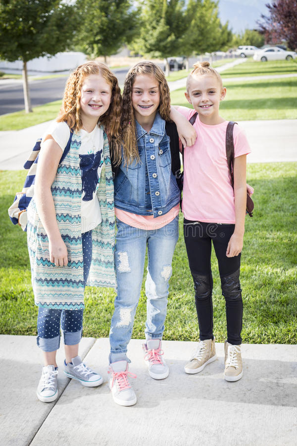 Three cute school girls heading off to school stock image