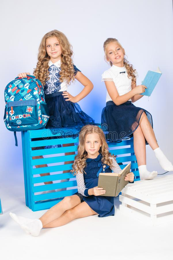 Three cute schoolgirls in a beautiful trendy school uniform with a backpack, books and notebooks with blue chair stock image