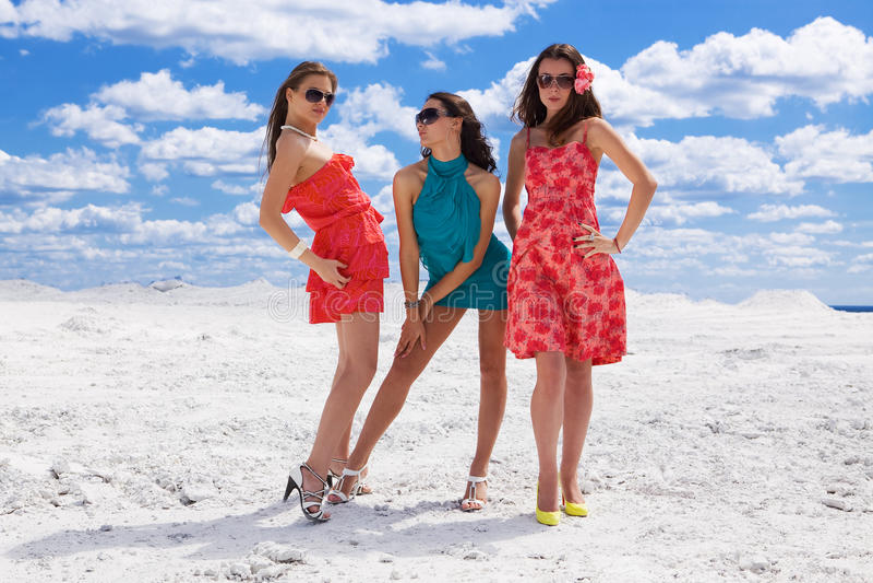Three Cute girls on the snow posing royalty free stock photos