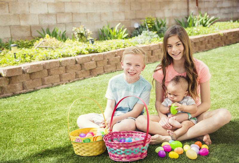 Three cute smiling kids collecting eggs on an Easter Egg hunt outdoors. Easter Holiday lifestyle photo. Three cute smiling kids collecting eggs on an Easter Egg stock photo