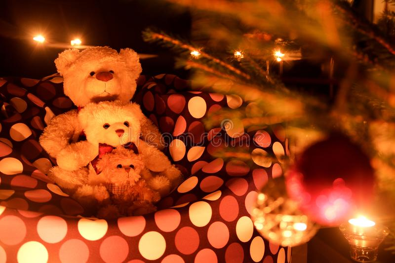 Three cute teddy bears by the Christmas tree. Three cute teddy bears are sitting by the Christmas tree and watching, how beautiful it is. Enjoying the cosy royalty free stock images