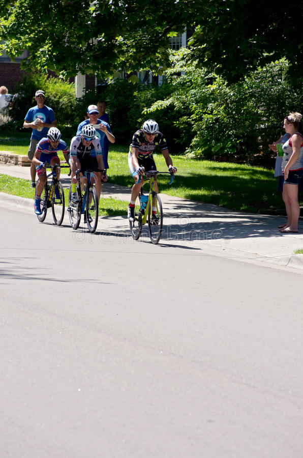 Three Cyclists Lead at Stillwater Criterium. Stillwater, Minnesota/USA - June 21, 2015: Cyclists Kevin Girkins (front) Ben Hill (middle) and Fabrizio Von Nacher royalty free stock photography