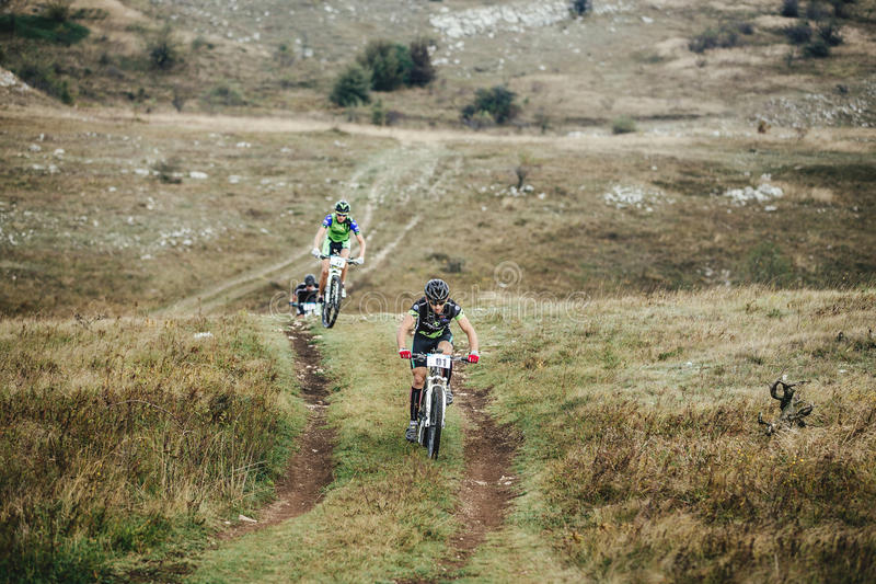 Three cyclists on mountain bikes rides of uphill royalty free stock images