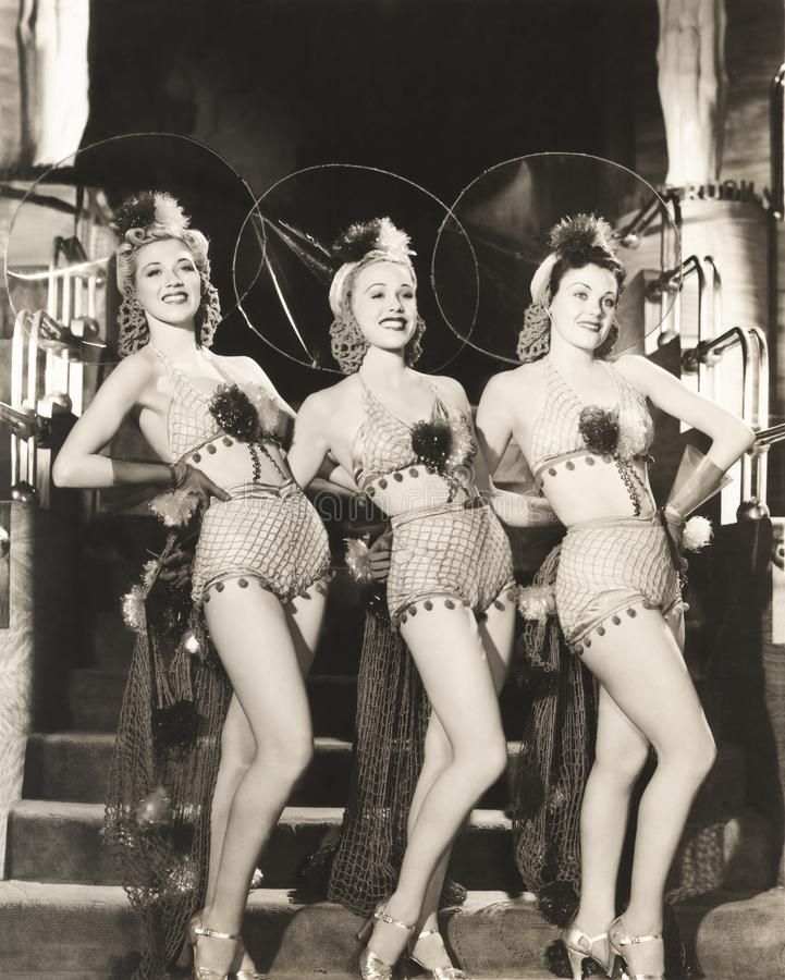 Three dancers in fishnet costumes stock image