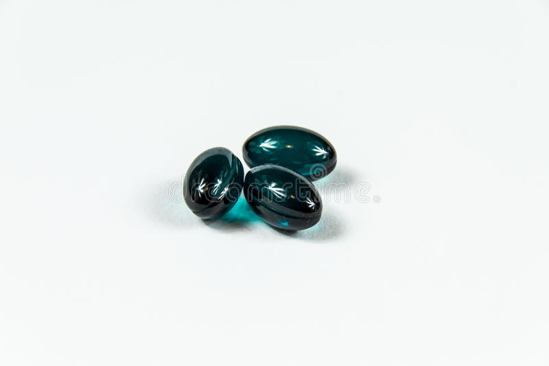 Three dark green soft gelatine capsules. Three dark green soft gelatine capsules in bright light royalty free stock photos