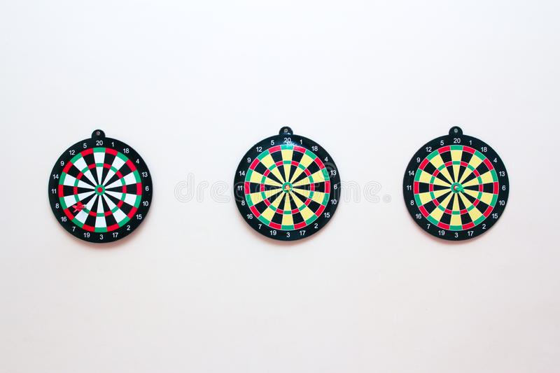 Three Dartboard with a dart on a gray wall close up royalty free stock images
