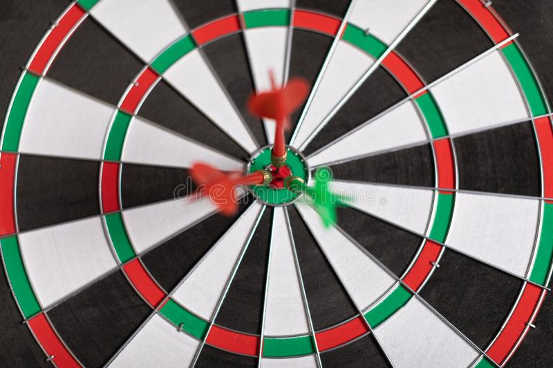 Three Darts hit red target on the target right close-up stock photography