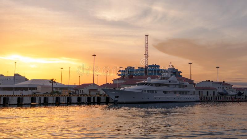 Three-deck yacht in the port, illuminated by a beautiful orange sunset sun. Background with copy space stock photos