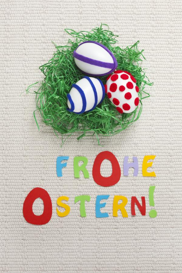 Three decorated Easter eggs and colorful letters saying `Happy Easter` in German on an ecru background. royalty free stock photo