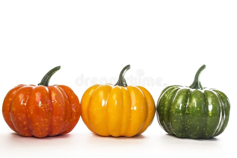 Three decorative artificial little pumpkins on a white background. Multi-colored vegetables of orange-yellow-green color for home stock image