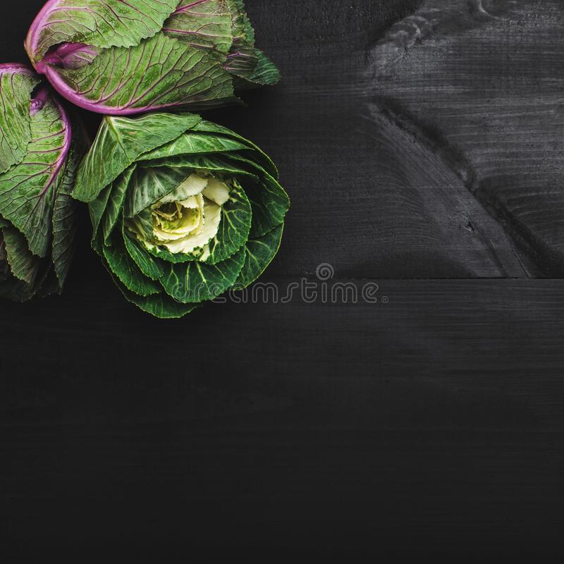Three decorative cabbages, fresh vegetables. Background of dark wooden texture stock image