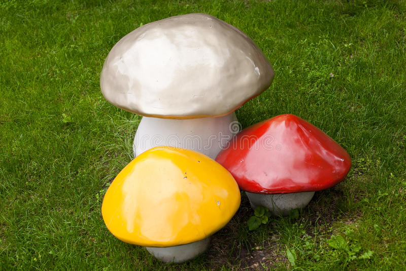 Three decorative mushroom - decoration on the lawn. Made of plastic like a natural look - three mushrooms: one large - gray, and two smaller, red and yellow stock images