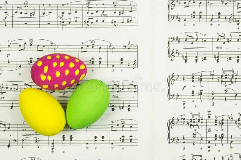 Three decorative painted Easter eggs on sheet with music notes as background. stock photo