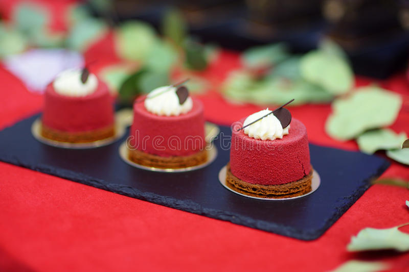 Three delicious red velvet cupcakes on dessert table royalty free stock photography
